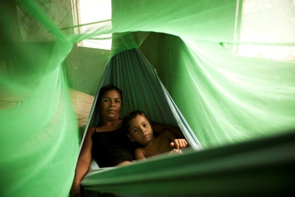 Mother and child under mosquito bed nets